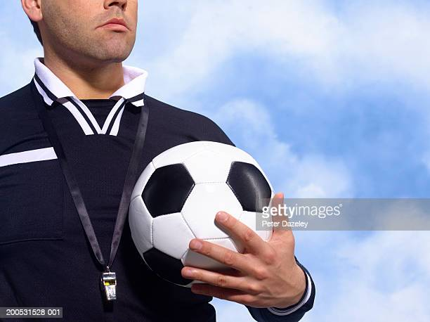Referee holding football, with whistle around neck, mid section