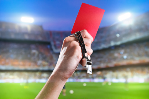 Referee holding up a red card and whistle inside a stadium 185966428