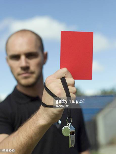 a referee holding up a red card - soccer referee stock photos and pictures