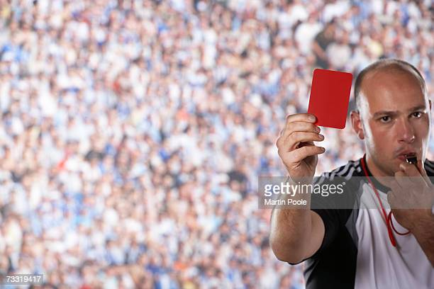 Referee holding up red card on field