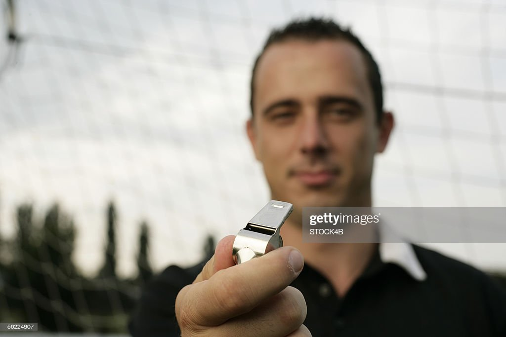 Referee holding Whistle : Stock Photo