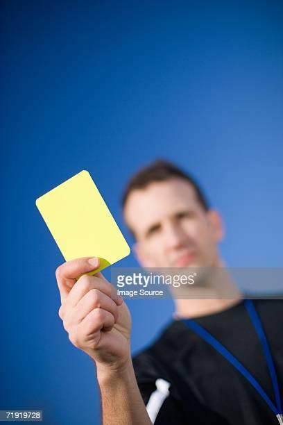 Schiedsrichter holding Gelbe Karte