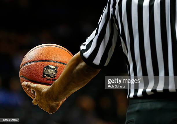 A referee holds a ball with the Coaches vs Cancer logo in the first half of a game in the Coaches vs Cancer Classic men's basketball tournament at...