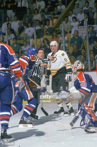 A referee holds back Canadian ice hockey player Cam Neely of the Boston Bruins and tries to wave off Steve Smith of the Edmonton Oilers during an...