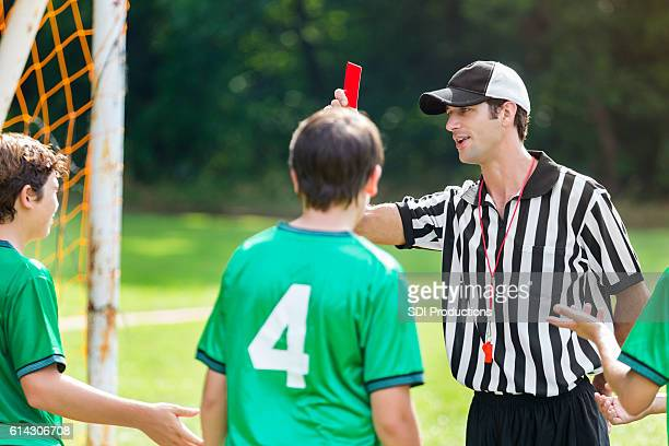 Referee holds up red card in soccer game