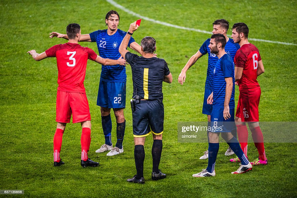 Referee holds up red card : Stock-Foto