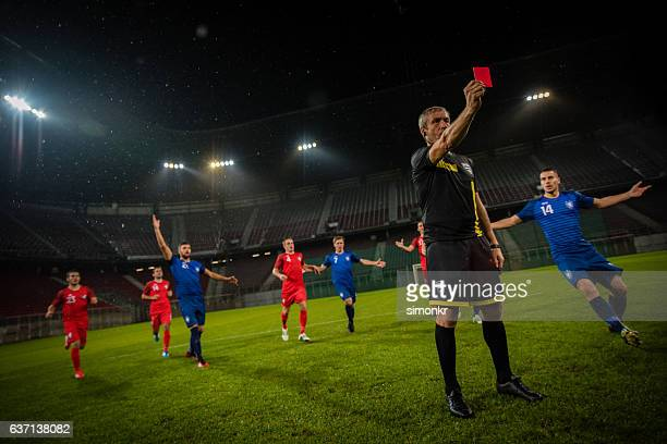 referee holds up red card - referee stock photos and pictures