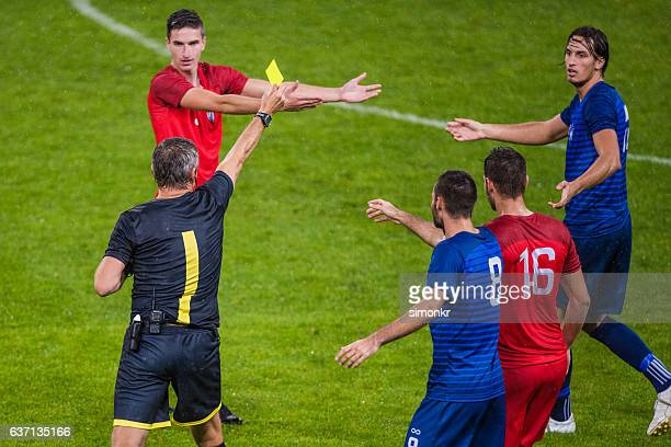 referee holds up yellow card - referee stock photos and pictures