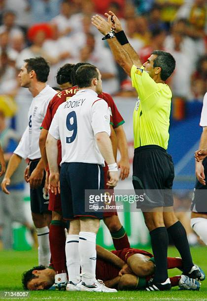 Referee Horacio Elizondo of Argentina appeals for a stretcher as Ricardo Carvalho of Portugal lies on the pitch in pain during the FIFA World Cup...