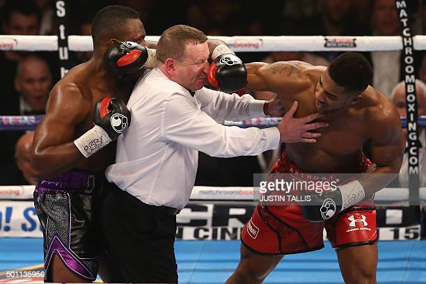 TOPSHOT Referee Howard Foster tries to separate British boxer Dillian Whyte and British boxer Anthony Joshua after the bell had rang in round one...