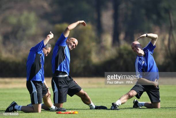 Referee Howard Webb and his assitants Darren Cann and Michael Mullarkey stretch following a training session at the Final Referees Media Day for the...
