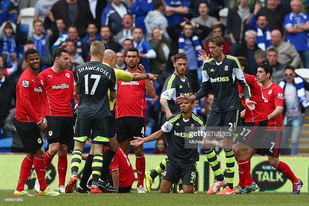 Referee Howard Webb awards a penalty after Peter Odemwingie (grounded) of Stoke City is fouled during the Barclays Premier League match between Cardiff City and Stoke City at the Cardiff City Stadium on April 19, 2014 in Cardiff, Wales.