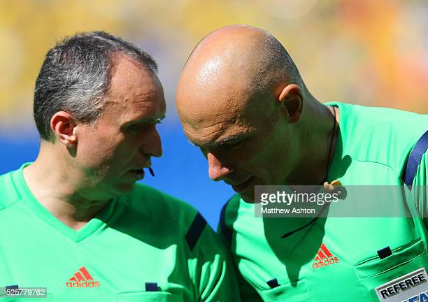 Referee Howard Webb confers with assistant Darren Cann