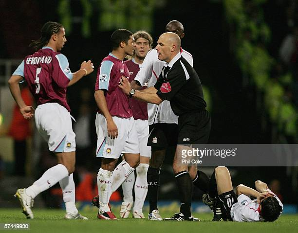 Referee Howard Webb holds back Hayden Mullins of West Ham United as he clashes with Luis Garcia of Liverpool during the Barclays Premiership match...
