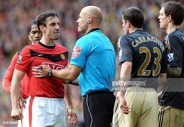 Referee Howard Webb holds Manchester United's English defender Gary Neville await from Liverpool's English defender Jamie Carragher during their...