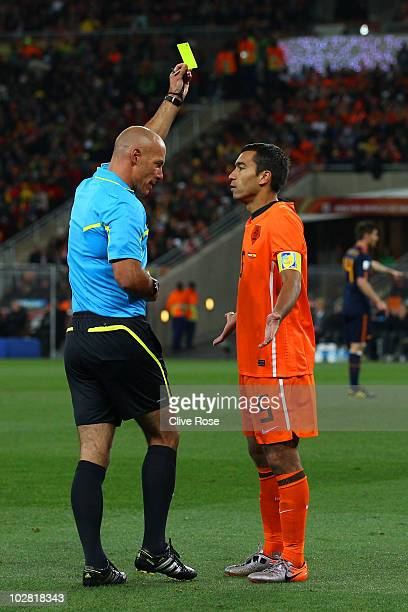 Referee Howard Webb issues Giovanni Van Bronckhorst of the Netherlands a yellow card during the 2010 FIFA World Cup South Africa Final match between...