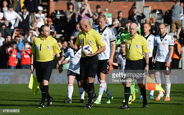 Referee Howard Webb leads out the teams with his assistants Darren Cann and Mike Mallarkey before the Barclays Premier League match between Fulham...