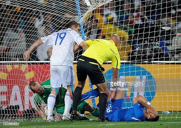 Referee Howard Webb looks down at Fabio Quagliarella of Italy as the player puts his hands over his face after trying to get the ball from goalkeeper...