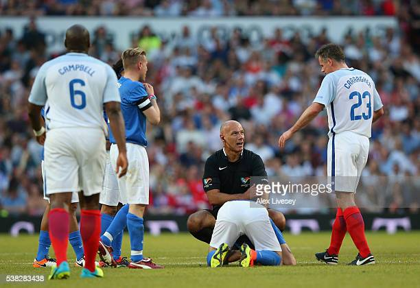 Referee Howard Webb looks to Jamie Carragher of England after a tackle on Shayne Ward of Rest of the World during the Soccer Aid 2016 match in aid of...