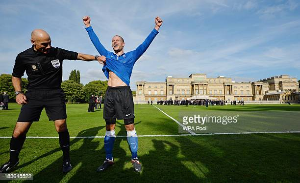 Referee Howard Webb shares a joke with Polytechnic FC player Bojan Jelovac as he celebrates scoring the first goal in the grounds of Buckingham...