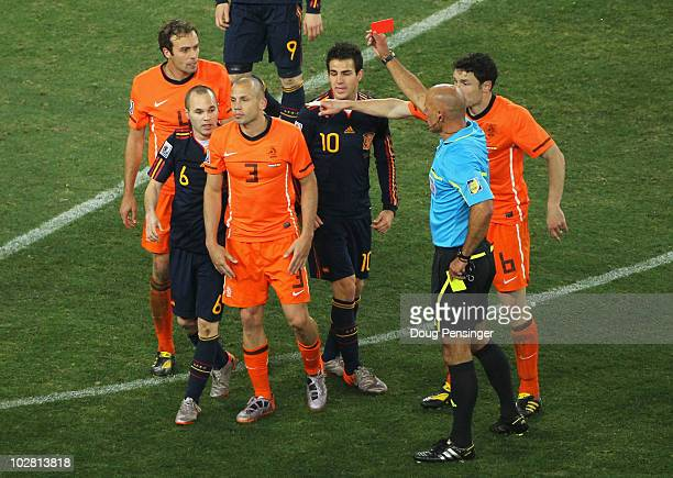 Referee Howard Webb shows John Heitinga of the Netherlands a red card following his second bookable offence during the 2010 FIFA World Cup South...