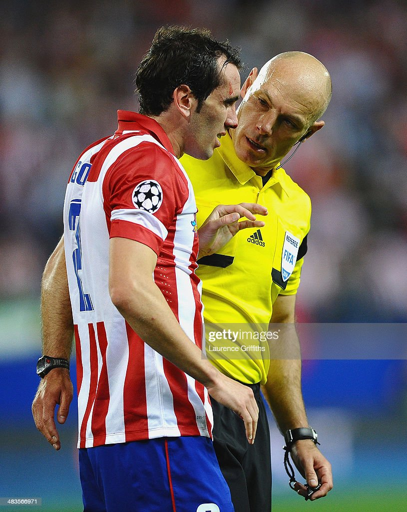 Referee Howard Webb talks to Diego Godin of Club Atletico de Madrid during the UEFA Champions League Quarter Final second leg match between Club Atletico de Madrid and FC Barcelona at Vicente Calderon Stadium on April 9, 2014 in Madrid, Spain.