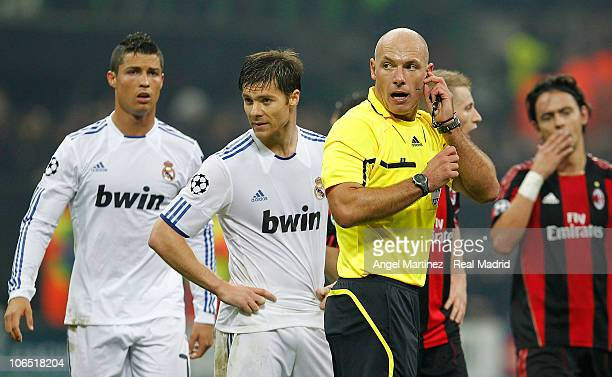 Referee Howard Webb talks to his assistant beside Xabi Alonso and Cristiano Ronaldo of Real Madrid during the UEFA Champions League Group G match...