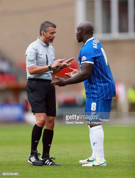 Referee Iain Williamson with Gillingham's Adebayo Akinfenwa during the Sky Bet Football League One match at the County Ground Swindon