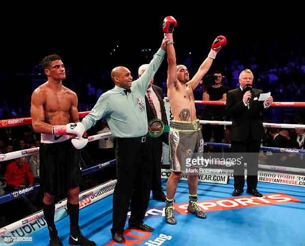 Referee Ian John Lewis holds aloft Craig Cunningham Of England arm after he stopped Anthony Ogogo Of England in the 8th Round during their WBC...
