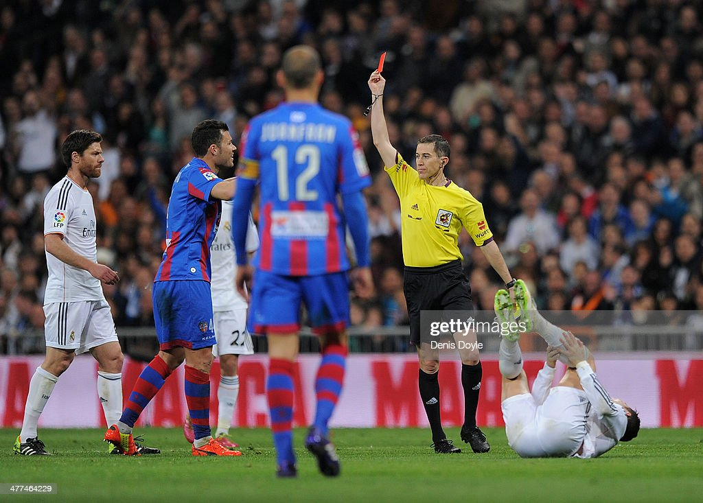 Referee Ignacio Iglesias Villanueva sends off David Navarro (2nd L) of Levante UD after he fouled Cristiano Ronaldo (R) of Real Madrid CF during the La Liga match between Real Madrid CF and Levante UD at Santiago Bernabeu stadium on March 9, 2014 in Madrid, Spain.