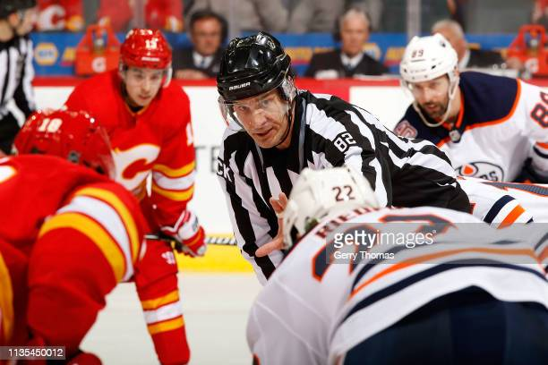 A referee instructs players of the Calgary Flames and Edmonton Oilers during an NHL game on April 6 2019 at the Scotiabank Saddledome in Calgary...