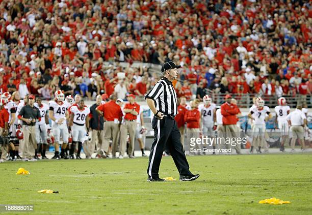 A referee is seen with penalty flags during the game between the Georgia Bulldogs and the Florida Gators at EverBank Field on November 2 2013 in...