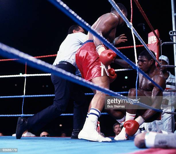 Referee Isidoro Rodriguez steps in to protect Britain's Frank Bruno as Tim Witherspoon wins the WBA World Heavyweight Title at Wembley Stadium in...