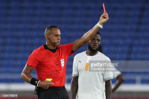Referee Ismail Elfath shows a red card after a second yellow card to Ivory Coast's midfielder Eboue Kouassi during the Tokyo 2020 Olympic Games men's...