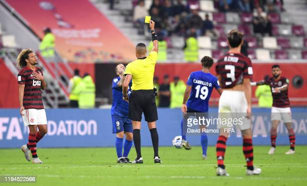 Referee Ismail Elfath shows Sebastian Giovinco of Al Hilal SFC a yellow card during the FIFA Club World Cup semifinal match between CR Flamengo and...
