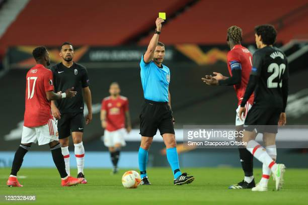 Referee Istvan Kovacs shows Paul Pogba of Manchester United a yellow card during the UEFA Europa League Quarter Final Second Leg match between...