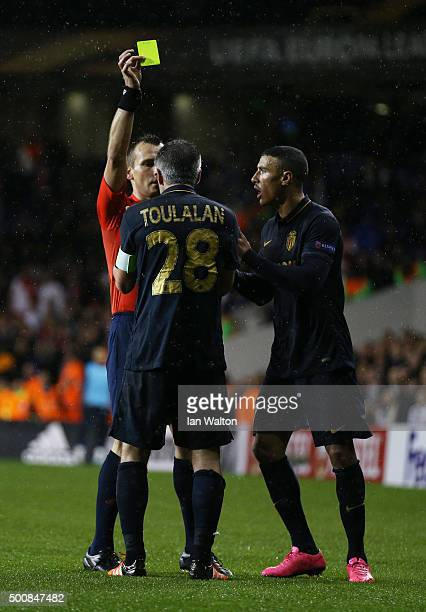 Referee Ivan Bebek of Croatia shows a yellow card to Jeremy Toulalan of Monaco after fouling Clinton N'jie of Spurs during the UEFA Europa League...