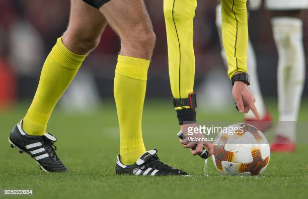 Referee Ivan Kruliak uses his aerosol spray to mark the position of the free kick during the UEFA Europa League Round of 32 Second Leg match between...