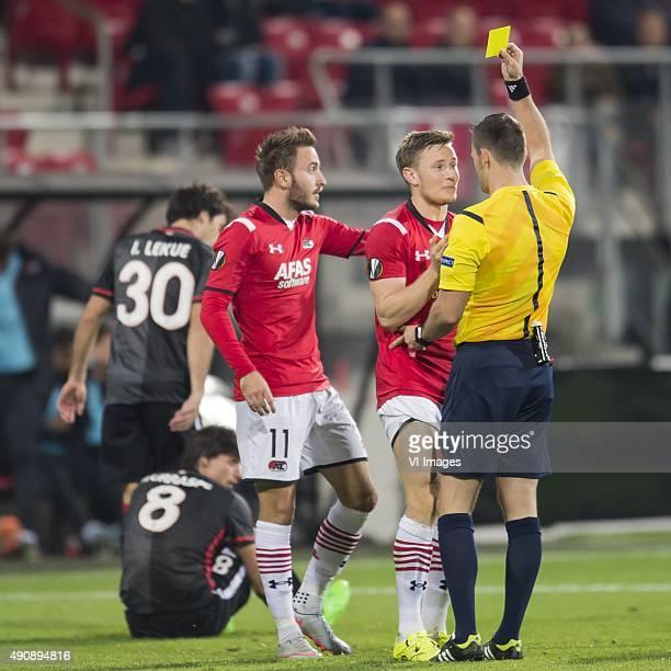Referee Ivan Kruzliak gives a yellow card to Mattias Johansson of AZ Alkmaar during the UEFA Europa League match between AZ Alkmaar and Athletic de...