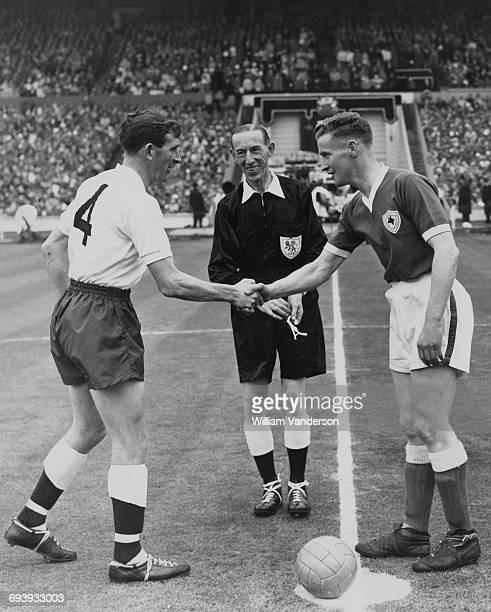Referee Jack Kelly looks on as Jimmy Walsh captain of Leicester City shakes hands with Danny Blanchflower captain of Tottenham Hotspur before the...
