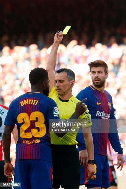 Referee Jaime Latre shows a yellow card to Barcelona's French defender Samuel Umtiti during the Spanish League football match between FC Barcelona...