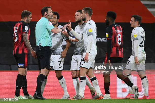 Referee James Linington is surrounded by Swansea players during the Sky Bet Championship match between AFC Bournemouth and Swansea City at Vitality...