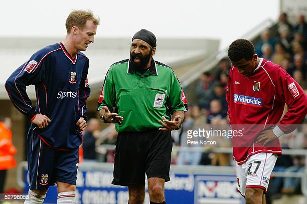 Referee Jarnail Singh talks to Lee Williamson of Northampton Town and Peter Gain of Lincoln City during the Coca Cola League Two match between...