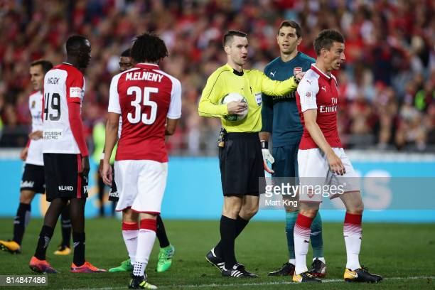 Referee Jarred Gillett gives the Wanderers a free kick close to goal after Arsenal goalkeeper Emiliano Martinez picked up the ball after being passed...