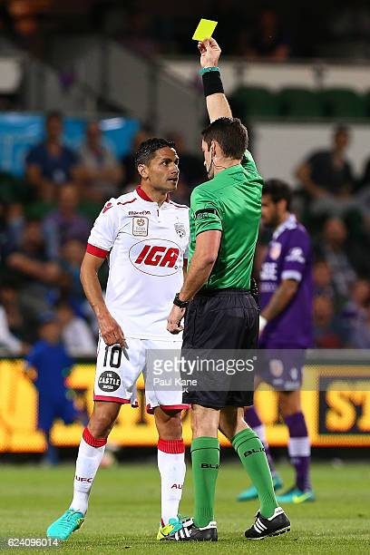 Referee Jarred Gillett issues a yellow card to Marcelo Carrusca of Adelaide during the round seven ALeague match between the Perth Glory and Adelaide...
