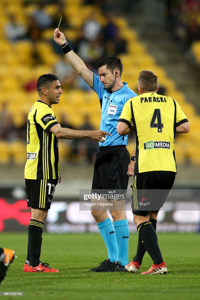 Referee Jarred Gillett shows Ali Abbas of the Phoenix a yellow card during the round four A-League match between the Wellington Phoenix and the Brisbane Roar at Westpac Stadium on October 28, 2017 in Wellington, New Zealand.
