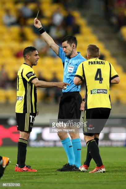 Referee Jarred Gillett shows Ali Abbas of the Phoenix a yellow card during the round four ALeague match between the Wellington Phoenix and the...