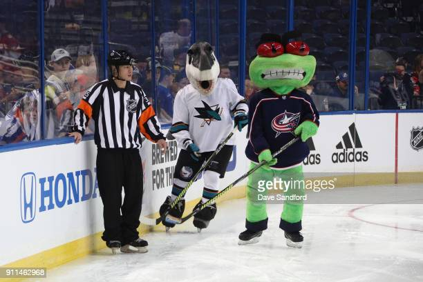 Referee Jason Hsu looks on as SJ Sharkie of the San Jose Sharks and Stinger of the Columbus Blue Jackets skate by during the PreGame Mascot Showdown...