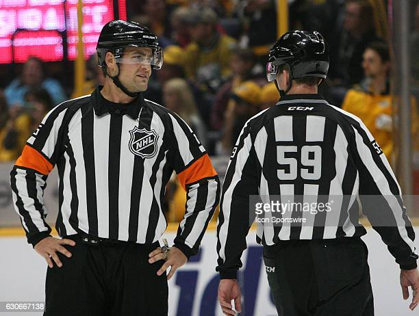 Referee Jean Hebert and linesman Steve Barton are shown during the NHL game between the Nashville Predators and the Chicago Blackhawks held on...