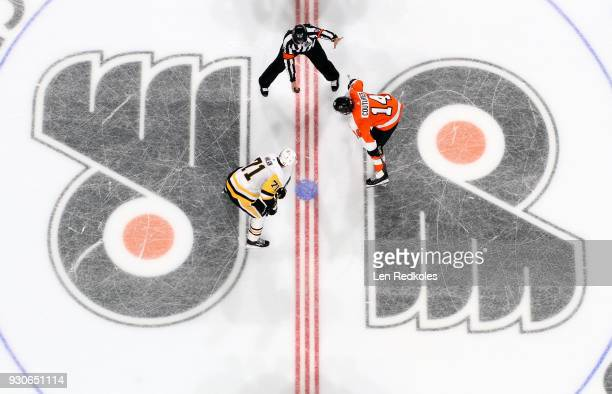 Referee Jean Hebert prepares to drop the puck on a faceoff between Sean Couturier of the Philadelphia Flyers and Evgeni Malkin of the Pittsburgh...